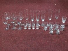 A collection of vintage glasses including a set of six brandy glasses, four engraved shot glasses, a
