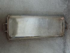 Two antique silver plated trays. One with two handles and bow motifs to the corners and