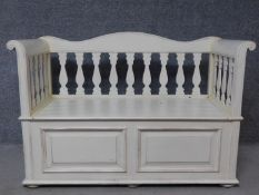 A distressed painted 19th century Northern European style box settle with hinged seat enclosing