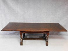 A Jacobean style oak draw leaf refectory style dining table on stretchered turning tapering