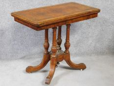 A Victorian burr walnut and satinwood inlaid card table with foldover top on quadruped column