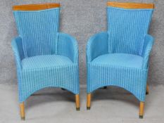 A pair of Lloyd Loom conservatory armchairs on circular teak brass capped supports. H.93cm