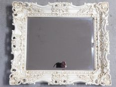 A white lacquered floral scrolling framed wall mirror fitted with bevelled plate. 68x58cm