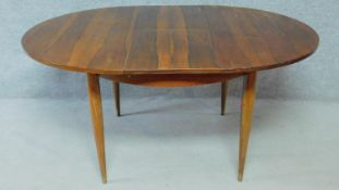 A vintage rosewood extending dining table on circular tapering supports fitted with swivelling