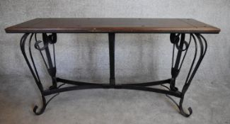 A rectangular console table with planked cleated hardwood top on metal cabriole scrolling