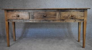 An antique country elm sideboard fitted with three frieze drawers on square tapering supports. H.