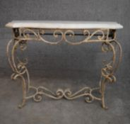 A mid 20th century white painted wrought iron console table with shaped marble top on scrolling