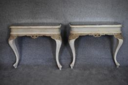 A pair of mid 20th century white painted and rococo carved console tables with inset mirrored tops