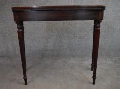 A late Georgian mahogany fold over top tea table on turned tapering supports. H.75x90x45cm (ext.