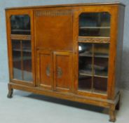 A mid 20th century carved oak bureau bookcase with central fitted secretaire section flanked by