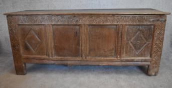 A 17th century carved oak coffer with hinged lidded top and panelled sides with lozenge decoration