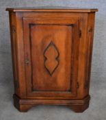 A Continental fruitwood corner cupboard with carved panel door on bracket feet. H.90x70x50cm