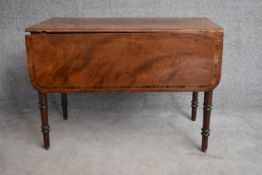 A 19th century mahogany and crossbanded drop flap Pembroke table on turned tapering supports. H.
