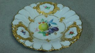 A Meissen handpainted and gilded fruit plate, with central cartouche depicting a lemon, plum,
