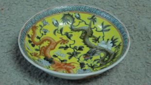 A Chinese yellow ground hand painted porcelain dish depicting two dragons, one red and one black.