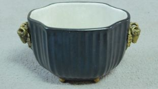 A Black antique style ribbed porcelain planter with two brass buck heads and mounted on brass