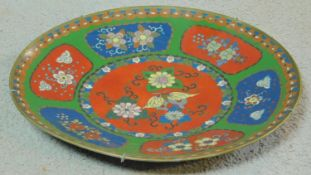 A Meji period Cloisonné enamel plate with red and blue panels on a green background decorated with