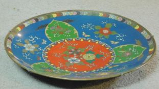A Meji period Japanese Cloisonné enamel plate with a red centre, pale blue background and three