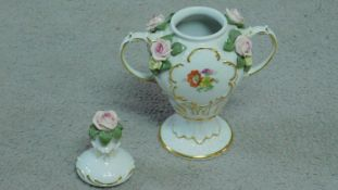 A German porcelain two handled lidded urn with hand painted floral motifs and sculpted porcelain