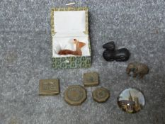 A collection of metal items and a carved carnelian deer. Including a bronze scroll weight in the