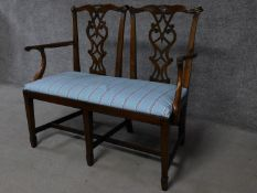 A George III Chippendale style mahogany double chair back settee with pierced splat and drop in seat