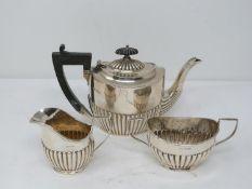 A matched three piece dragooned silver tea set. The ebony handled tea pot hallmarked: WA for William