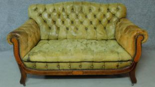 A late 19th century mahogany and satinwood inlaid two seater sofa in deep buttoned leather