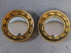 A pair of Regency miniature convex wall mirrors in beaded moulded gilt wood frames. 20x20cm