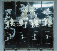A Japanese black lacquered three fold and four panel screen with mother of pearl and bone inlay.