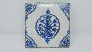 An 18th century Islamic blue and white hand painted ceramic tile with stylised floral design. 22x22
