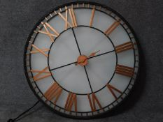 A large light in the form of a clock with gilded Roman numerals, wired and internally lit. 120x120cm