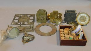 A collection of antique clock parts including clock movements, various clock dials and faces, a