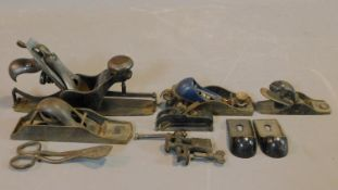 A collection of antique and vintage woodworking planes including a Record plane, a Stanley plane and