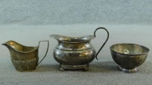 Three sterling silver items. Including an Art Deco milk jug on four button feet, hallmarked: EV