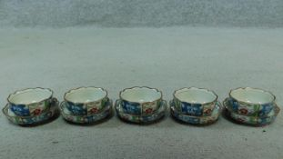 A wooden boxed set of five Oriental tea bowls and saucers with a floral design. Artist's signature