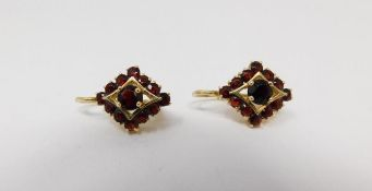 A pair of vintage 18 carat yellow gold and garnet diamond shaped earrings. Each set with thirteen