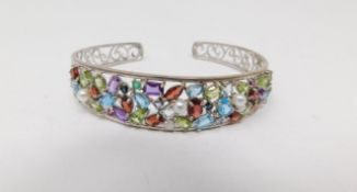 A multi gemstone and silver scrolling design pierced bangle. Set with forty eight mixed cut