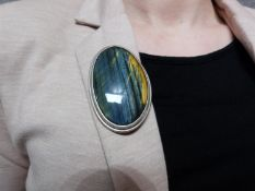 A bespoke Hawks Eye (possibly Pietersite) cabochon and white metal (tested silver) statement brooch,