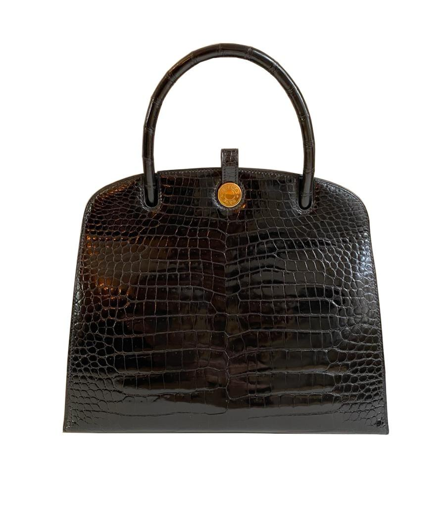 A Hermes Dalvy in black shiny crocodile with gold hardware and orange dustbag. W.30 x H.23 x D.10cm,