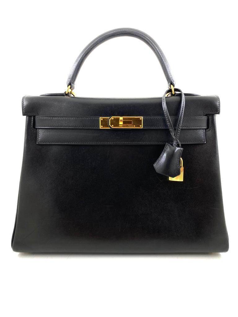A black Hermes Kelly in box leather with gold hardware, includes Dustbag, Lock, Clochette & Strap.