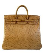 A gold Hermes Birkin Haut à Courroies (HAC) in ostrich leather with gold hardware, includes brown
