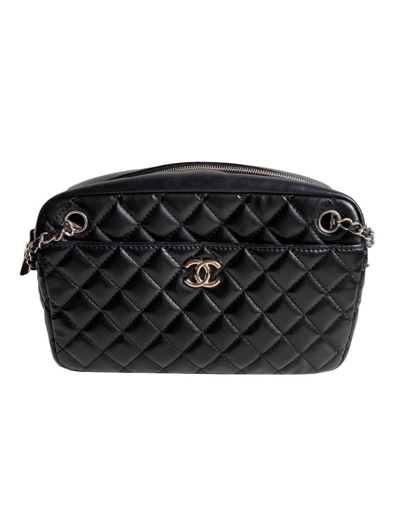 A Chanel Classic Camera Case in Black Lambskin with Silver Hardware, takes design inspiration from