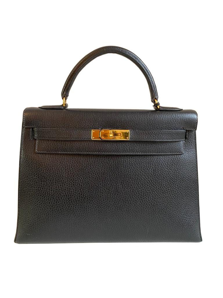 A black Hermes Kelly in Evergrain leather with gold hardware, includes Dustbag, Key (no lock),