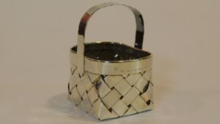 A Cartier silver basket of oval woven form with a scalloped edged handle, end marked to the side