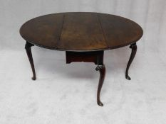 A mid Georgian Irish mahogany circular drop flap dining table with gateleg action on carved cabriole