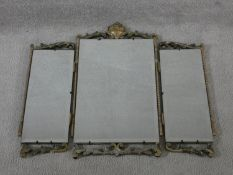 A mid century vintage triple section dressing mirror with painted and carved scrolling foliate frame