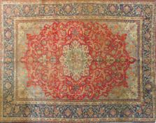 An antique Isfahan carpet with double central medallions on burgundy field with all over scrolling