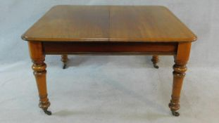 A 19th century mahogany extending dining table on turned tapering supports with extra leaf and