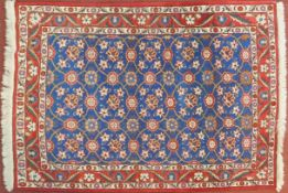 A Veramin Mina Khani style rug with repeating scrolling vine and floral decoration on a deep
