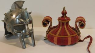 An articulated metal gladiator's helmet along with an Asian velour and gold brocade hat. H.28cm